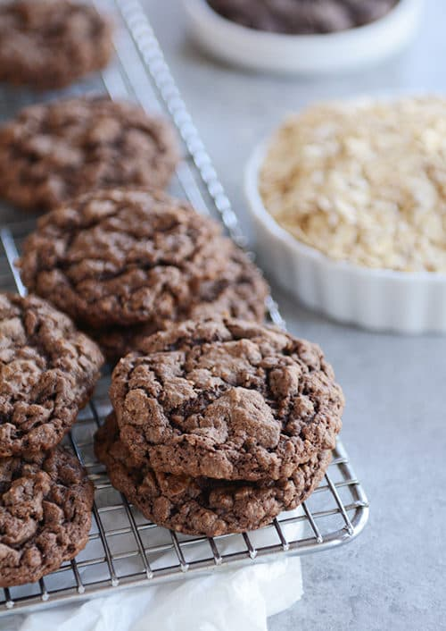 Chocolate oatmeal cookies stacked on a cooling rack.
