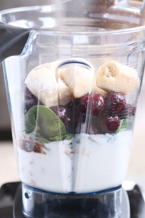 Layered ingredients in the blender for chocolate protein smoothie.