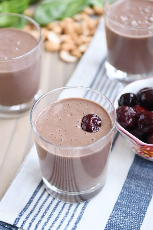 Chocolate protein smoothie in clear glass with cherry on top.