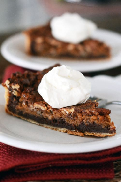 A white plate with a slice of chocolate caramel pecan pie with a dollop of whipped cream.