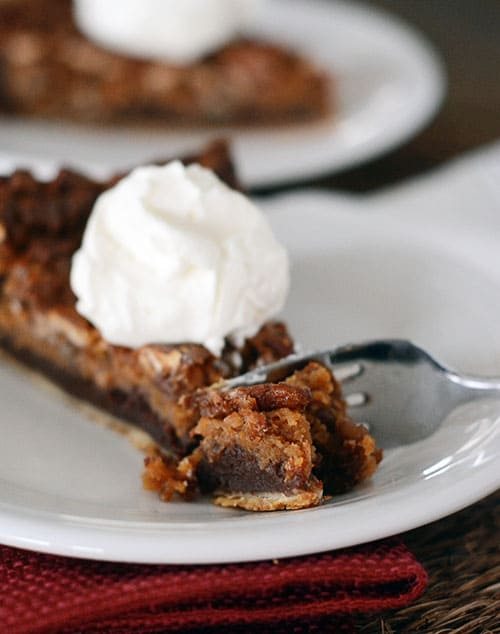 A slice of chocolate caramel pecan pie with a dollop of whipped cream on top and a fork taking a bite out..
