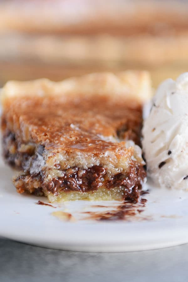A slice of gooey chocolate chip pie with a bite taken out on a white plate.