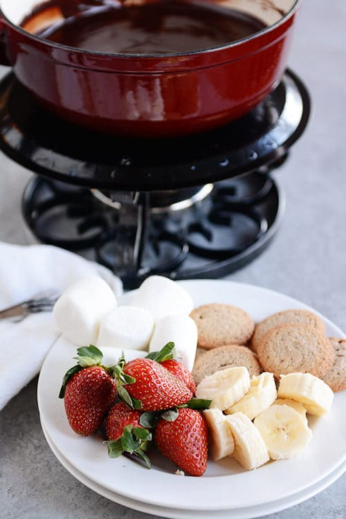 A plate of strawberries, marshmallows, banana slices, and cookies in front of a burner with a pot of chocolate fondue.