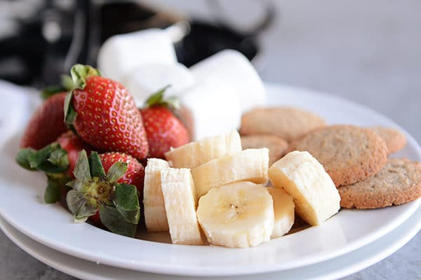 A plate of strawberries, marshmallows, banana slices, and cookies.