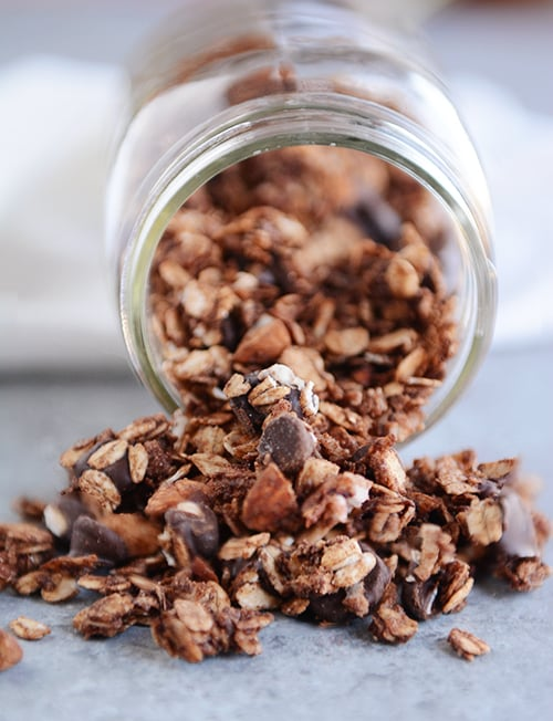 Chocolate granola spilling out of a mason jar.