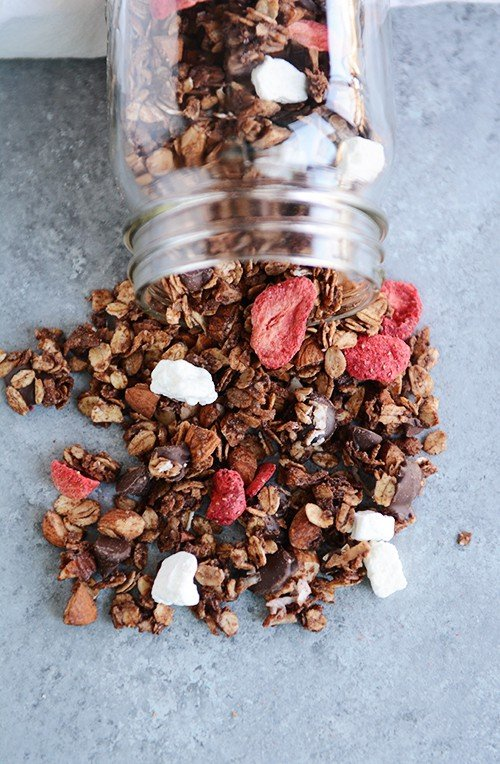 Dark chocolate and strawberry granola spilling out of a glass mason jar.