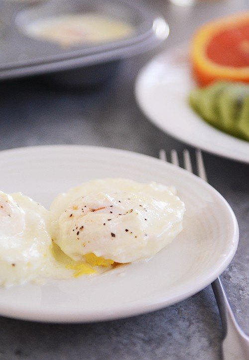 A white plate with a creamy cooked egg sprinkled with pepper.