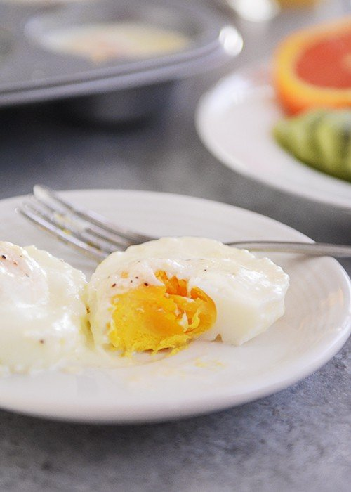 A white plate with a cooked egg with a bite taken out.