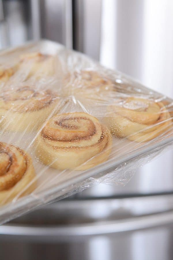 A pan of cinnamon rolls rising with saran wrap covering them.