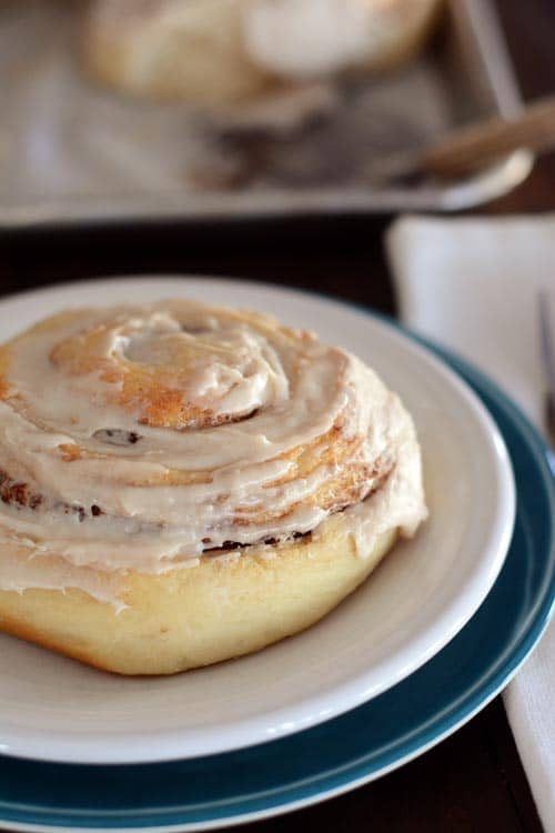 A frosted cinnamon roll sitting on a white plate.