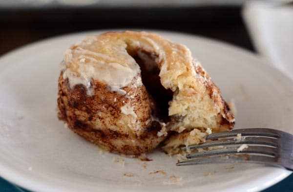 The middle part of a cinnamon roll on a white plate, with a fork on the side.