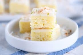 Toasted coconut lime bars stacked on white circle plate.