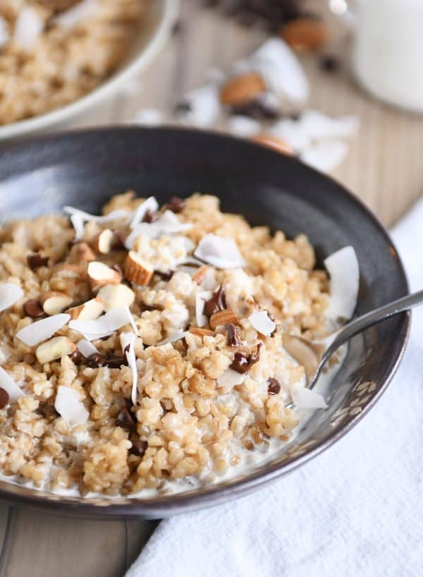 Coconut milk steel cut oats in brown bowl with chocolate chips, almonds and coconut.