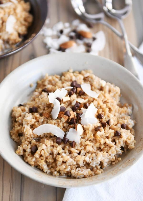 Coconut milk steel cut oats in white bowl with chocolate chips, almonds and coconut.