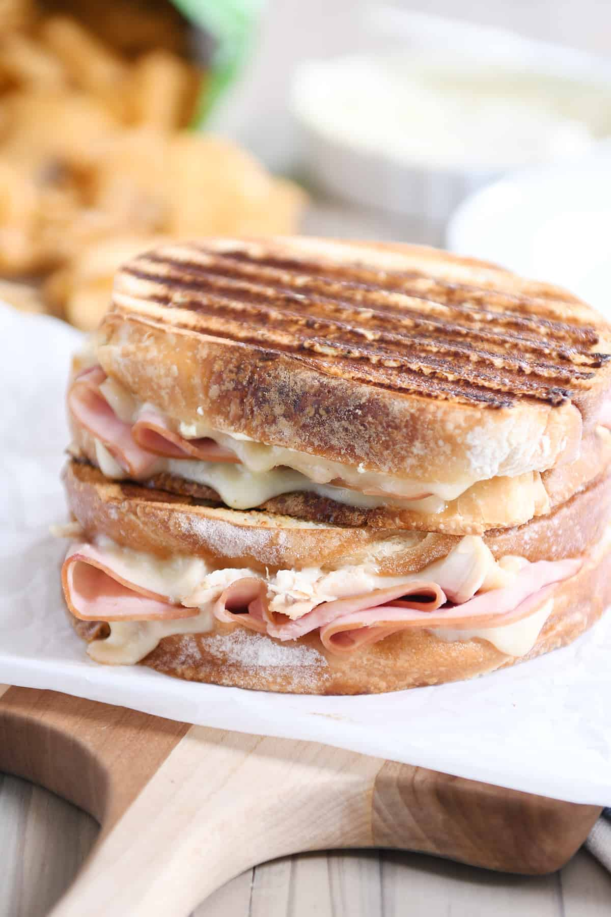 Two chicken cordon bleu panini sandwiches stacked on top of each other.