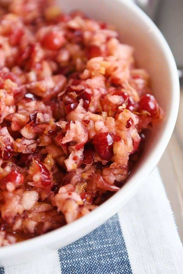 Close up view of fresh cranberry apple relish in white bowl.