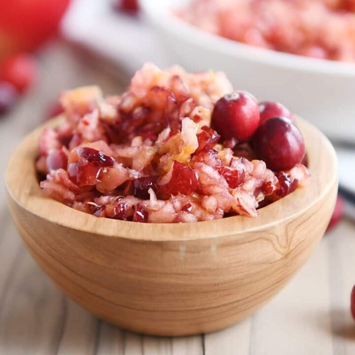 Fresh cranberry apple relish small serving in wood bowl.