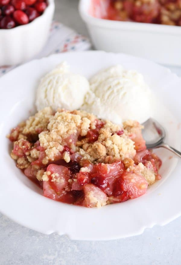 Close up view of bowl of cranberry pear crumble with vanilla ice cream.