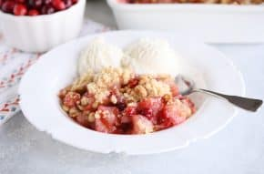 Bowl of cranberry pear crumble with vanilla ice cream.
