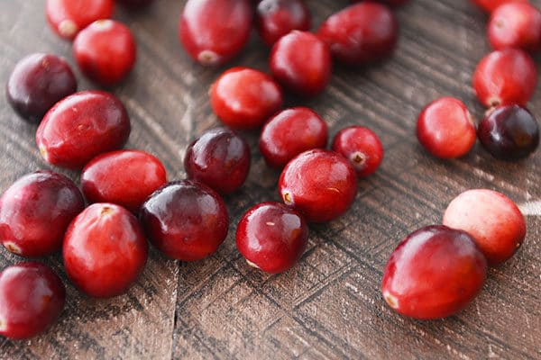 Fresh cranberries sprinkled on a countertop.