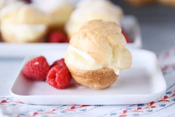 Perfect little foolproof cream puff on white plate with raspberries.
