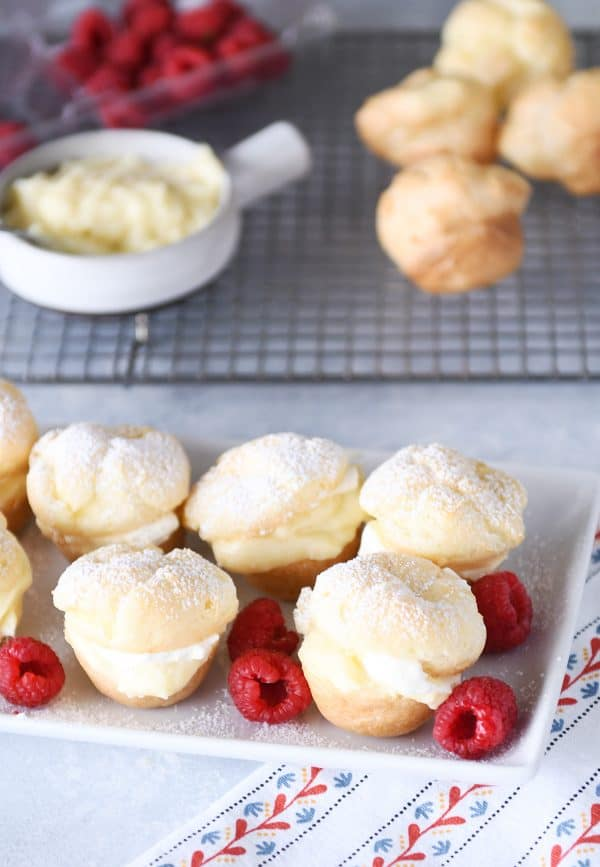 White tray of foolproof cream puffs and raspberries.