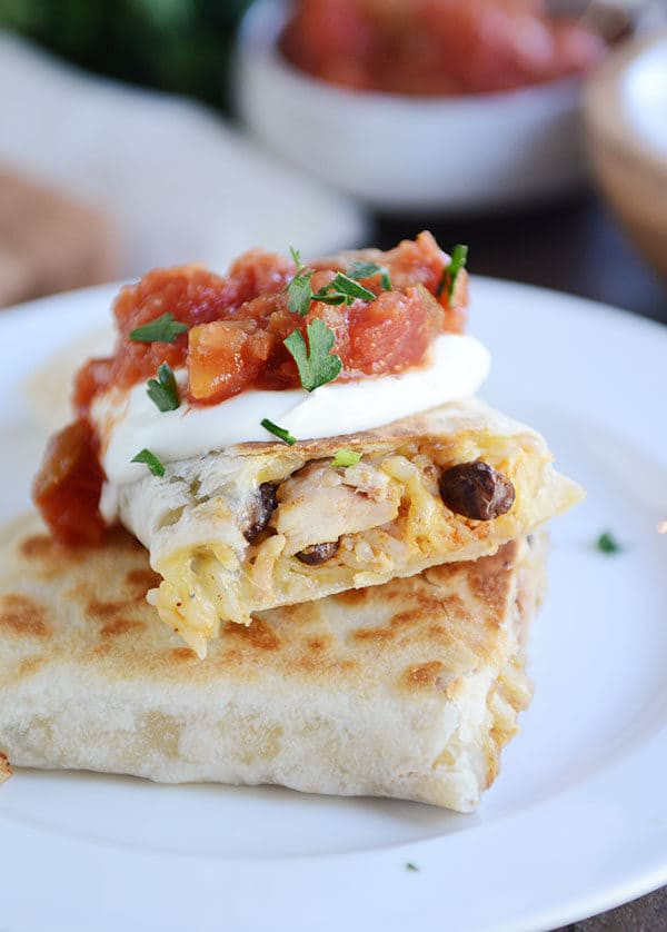 A griddled tortilla sitting on a white plate, filled with southwest ingredients and topped with sour cream, cilantro, and salsa.