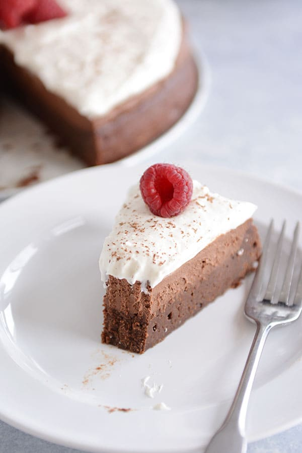 A slice of chocolate mousse torte with a bite taken out on a white plate.