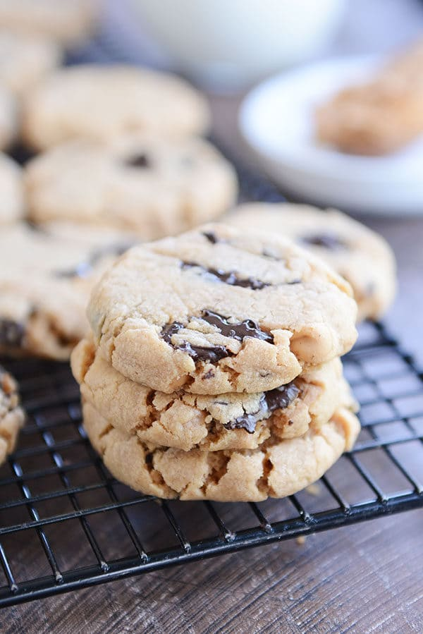 A stack of peanut butter chocolate chip cookies on a cooling rack.