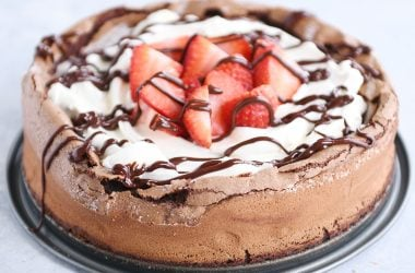 Fallen chocolate cake with whipped cream, strawberries, and chocolate drizzle.