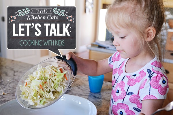 A little girl pouring salad into a white platter.