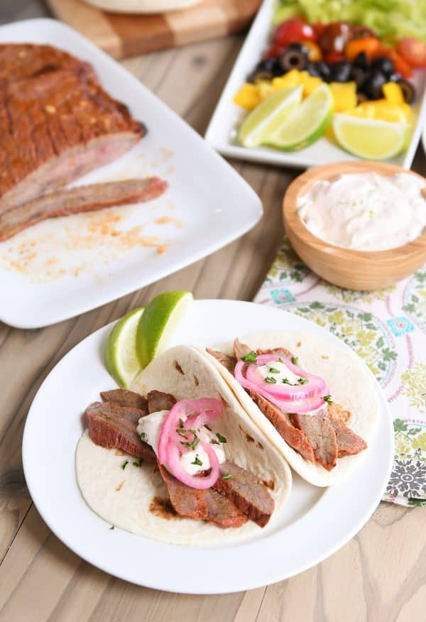 Flank steak fajitas on white plate with tortillas and pickled onion.
