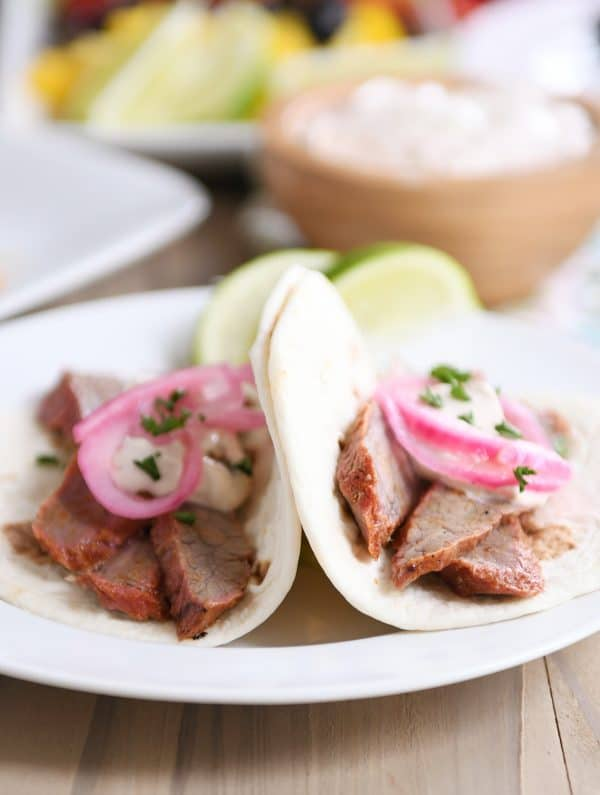 Steak fajitas in tortillas on white plate.