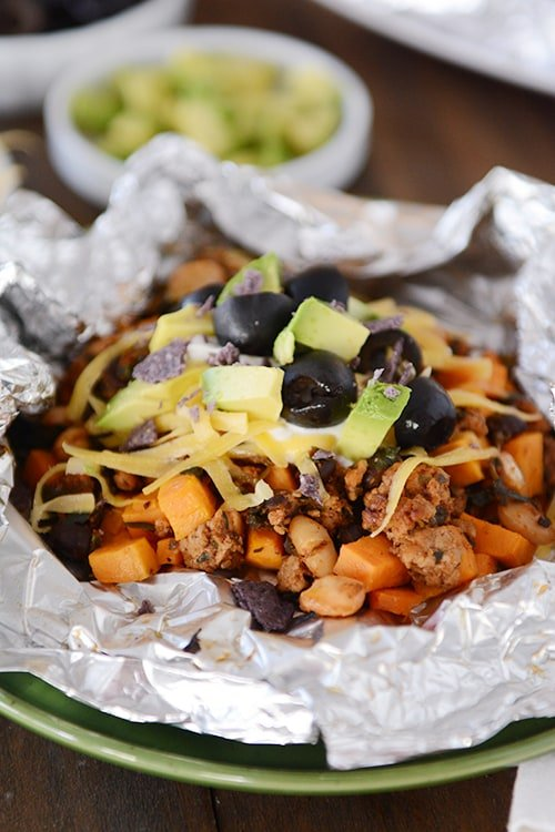 an open tinfoil packet of cooked sweet potato tacos toped with cheese, sour cream, avocado dices, and slices olives
