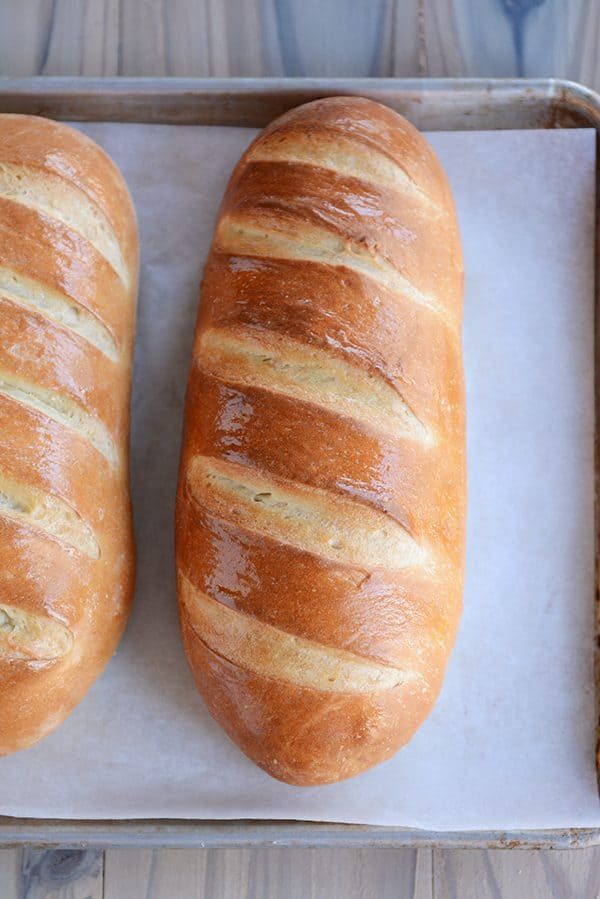 Two loaves of fresh homemade French Bread on a parchment-lined sheet pan.