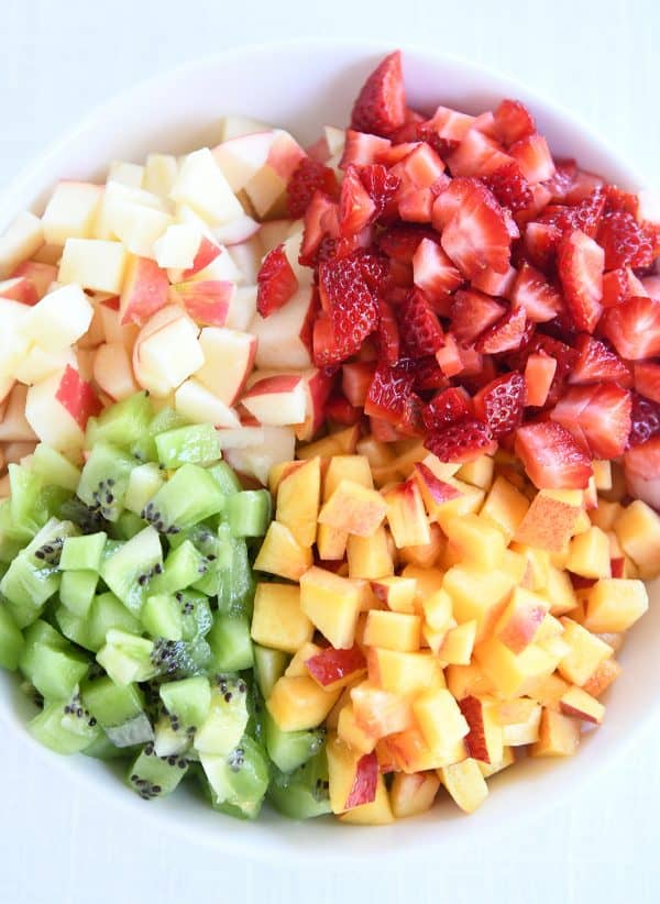 White bowl with diced apples, kiwis, peaches and strawberries.