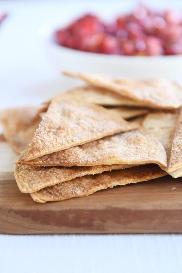 Baked cinnamon tortilla chips on wood cutting board.