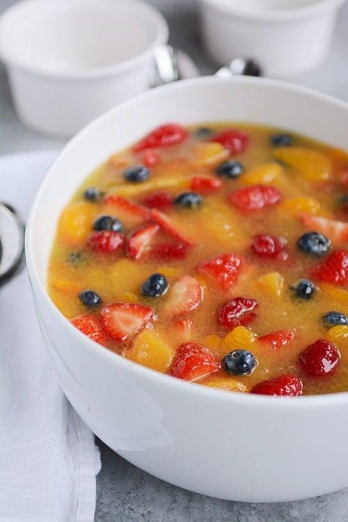A large white bowl full of berry and mandarin orange fruit soup.
