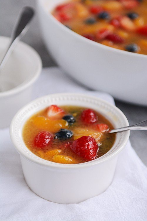 A small white bowl full of fruit soup with a spoon inside.