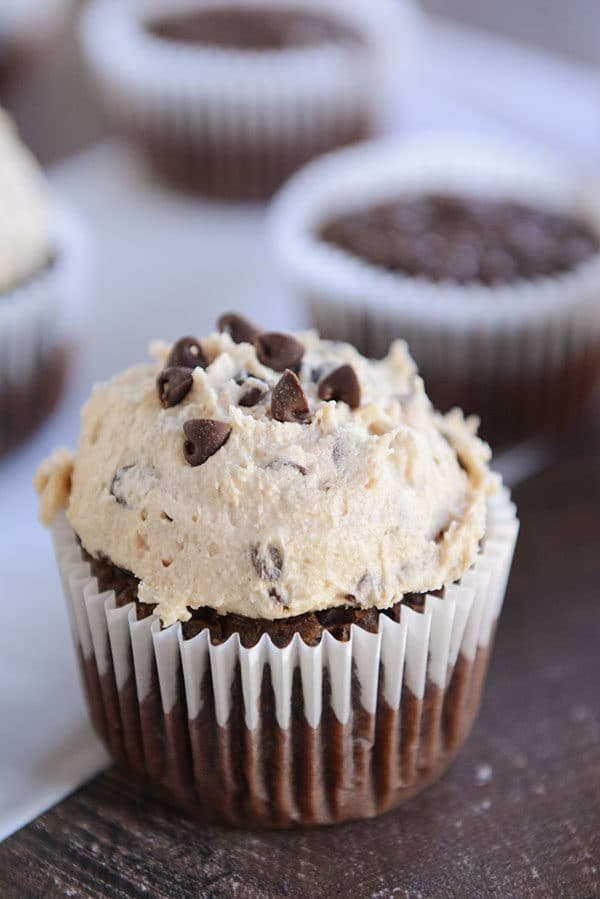A chocolate cupcake with a heaping scoop of cookie dough frosting on top.