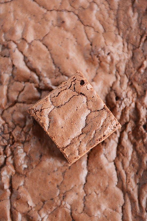 A cut up brownie on top of a pan of brownies.