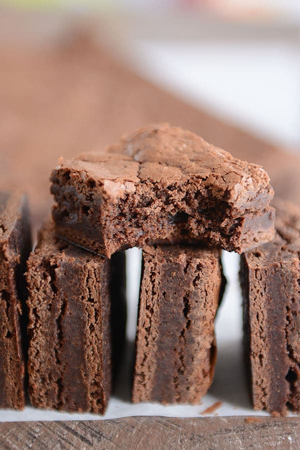Three brownies stacked on their sides with another brownie with a bite taken out on top.