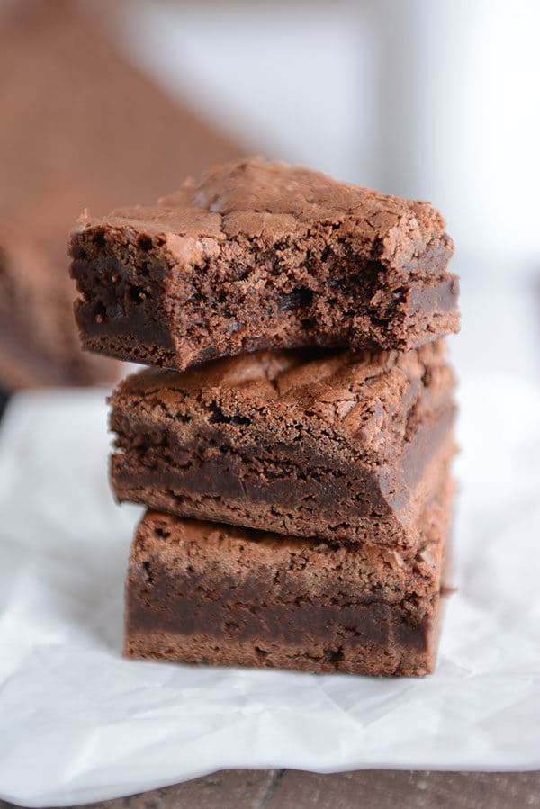 A stack of three brownies with a bite taken out of the top brownie.