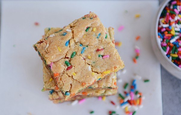 sprinkle-filled blondie bars stacked on each other on a piece of parchment