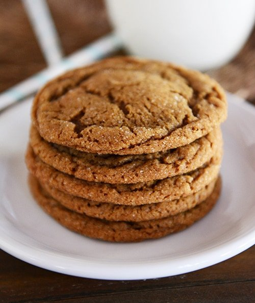 A stack of five brown molasses cookies on a white plate.