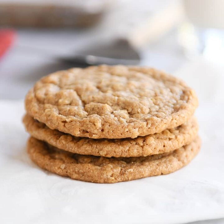Three gingerbread oatmeal cookies stacked on white napkin.
