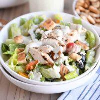 White bowl of chopped Greek chicken salad with tzatziki dressing.