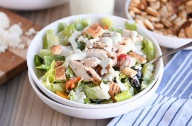 White bowl of chopped Greek chicken salad with tzatziki dressing.