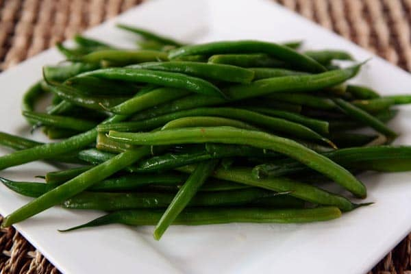 A white platter with a large serving of cooked green beans.