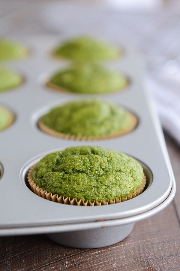 green baked muffins in a muffin tin